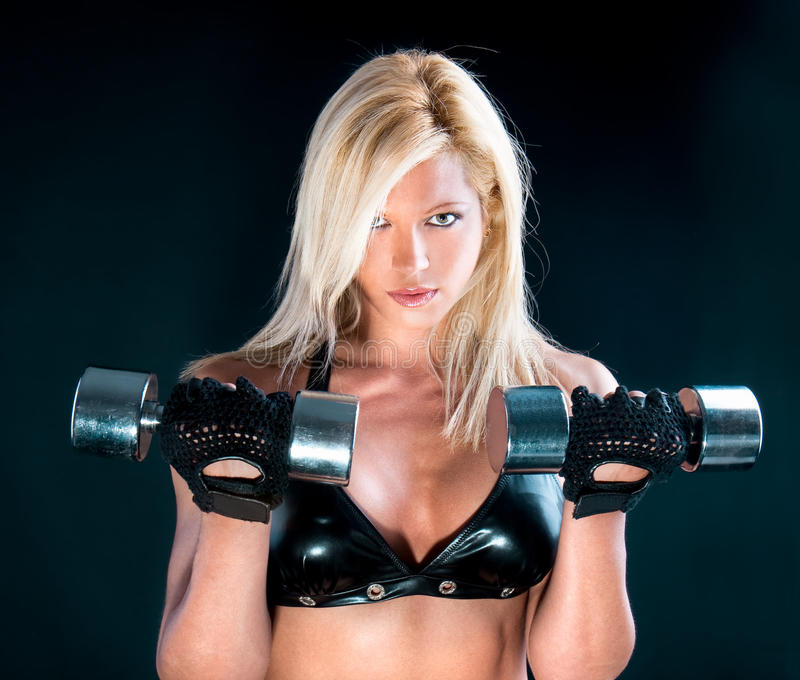 Lovely fitness instructor with dumbbells. Over black stock photo
