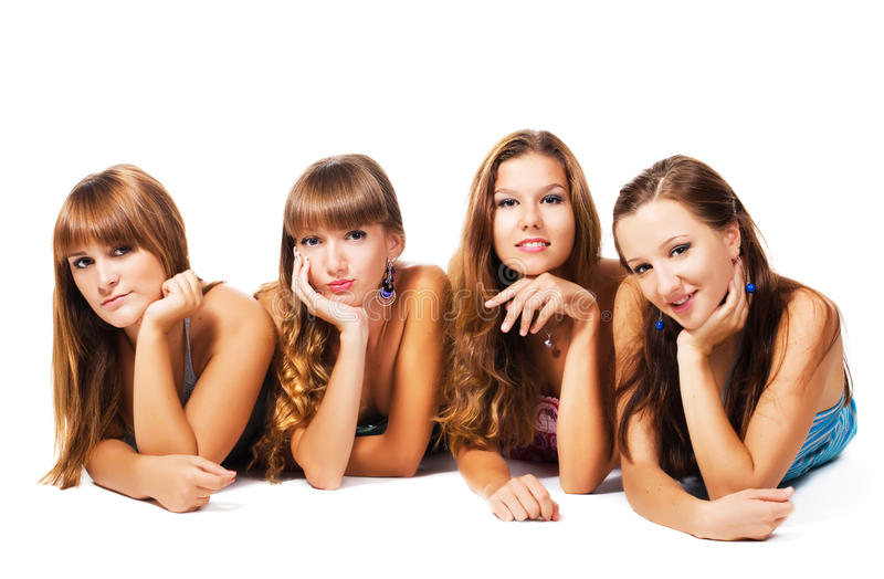 Lovely friends. Four lovely girls laying on the floor together. Isolated on white background royalty free stock photo