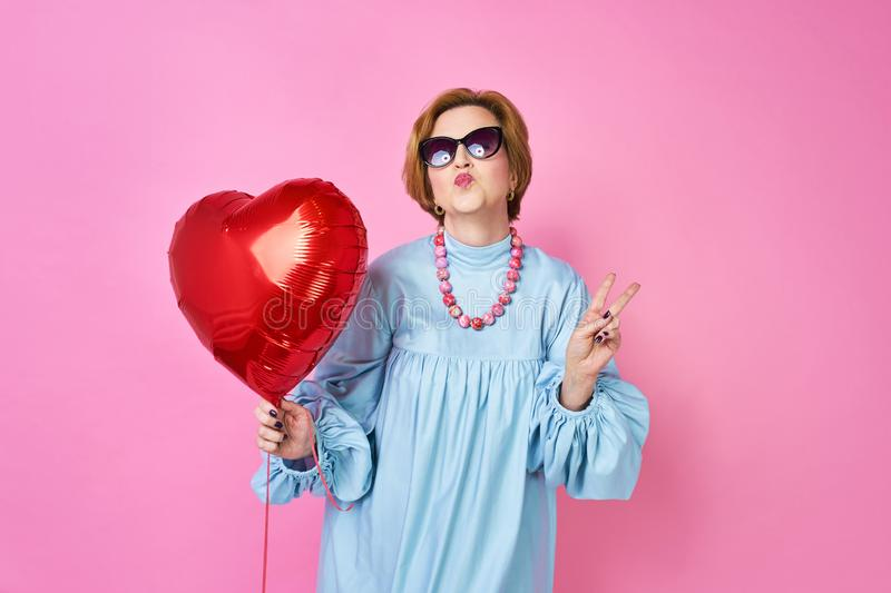 Lovely funky old woman blows a kiss. Elderly people. an outpost for dating sites, a wedding agency. stock photos