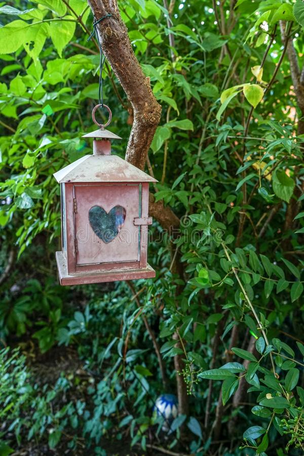 Small little decoration house with heart shaped window in garden. Lovely garden scene with small object hanging from tree stock photography