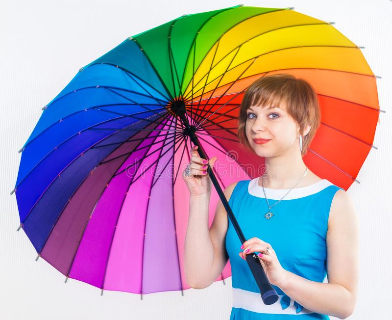 Lovely girl in blue dress under colorful positive rainbow Umbrella on white background. Studio shot, copy space stock photo
