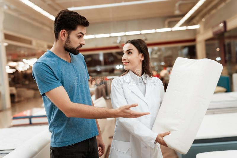Lovely girl consultant demonstrates orthopedic pillow to confident man in furniture store. Lovely girl consultant demonstrates orthopedic pillow to confident royalty free stock photo