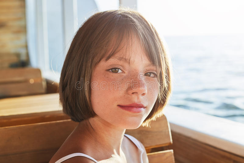 Lovely girl with dark eyes and freckles, dressed in summer dress, looking at camera while sitting at wooden bench of ship, admirin royalty free stock photos