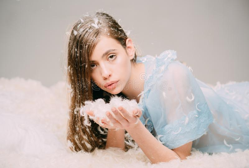 Lovely girl with long brunette hair holding handful of tiny feathers. Cute female teenager in blue lace nightgown lying stock photo