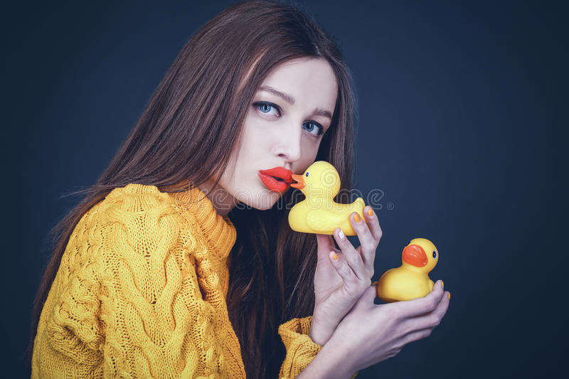 Lovely girl with red lips kissing yellow rubber ducks royalty free stock photos