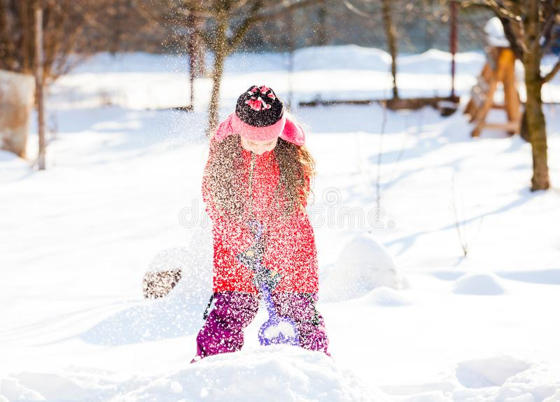 Lovely girl shoveling snow spilling it around. Lovely preschooler girl in a red jacket and winter hat holding blue plastic toy showel and spilling snow with it stock photos