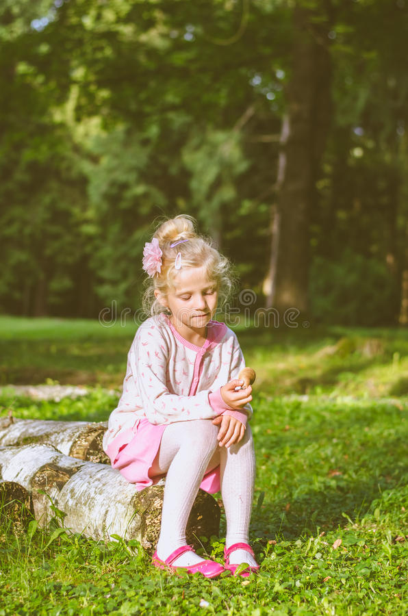 Lovely girl sitting in tree trunk royalty free stock photography