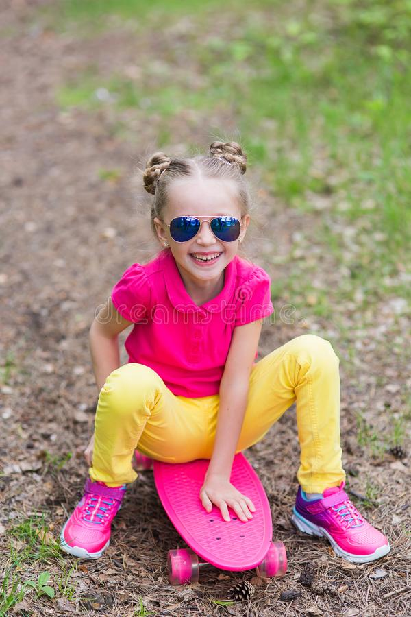 Sweet girl learns to ride a skateboard in the park. Lovely girl with a skateboard in the park in the summer royalty free stock photography