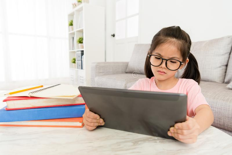 Lovely girl student using mobile digital tablet. Unhappy lovely girl student using mobile digital tablet looking online e-learning teaching video at home and stock image