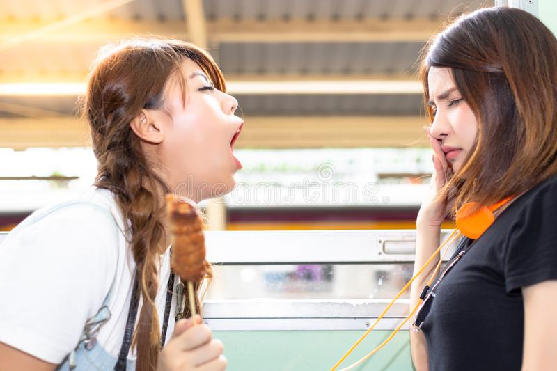 Lovely girl is using hand close her nose because her friend persecute and blow her bad breath to her. She eat some stink food. Pr. Etty women is suffering the stock image