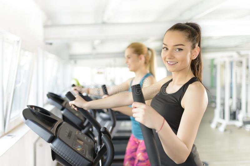 Woman Using Stepper. Lovely girl using stepper at gym royalty free stock image