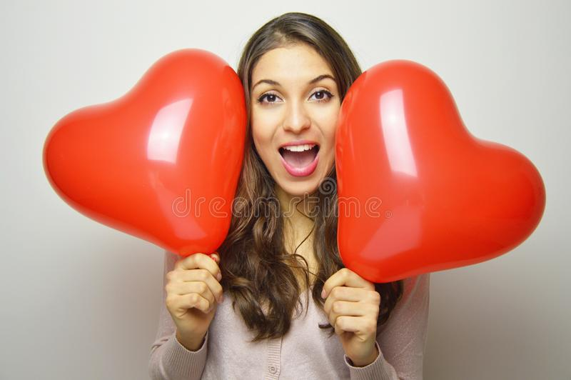 Lovely girl with Valentine heart balloons looking excited at the camera. Sweet young woman with two heart shaped balloons on white royalty free stock photo