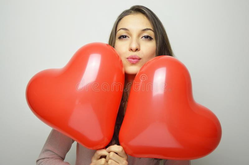 Lovely girl with Valentine heart balloons make air kiss and looking at the camera. Sweet young woman with two heart shaped balloon stock photography