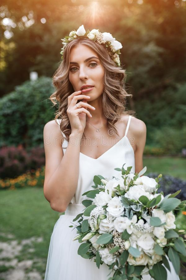 Lovely girl in wedding dress holding a bouquet of white flowers stock photo