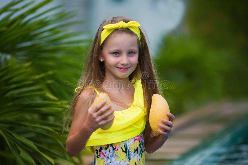 Lovely girl in yellow swimsuit holds yellow mango on vacation in the tropics stock image
