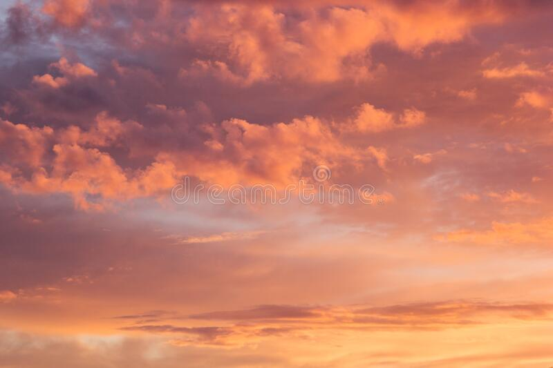 Lovely golden and pink clouds in blue heaven with soft haze on sunset as abstract background, texture. Lovely golden and pink clouds in blue heaven with soft stock photos
