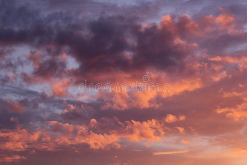 Lovely golden, purple and pink clouds in blue heaven with soft haze on sunset as abstract background, texture. Lovely golden, purple and pink clouds in blue royalty free stock photography
