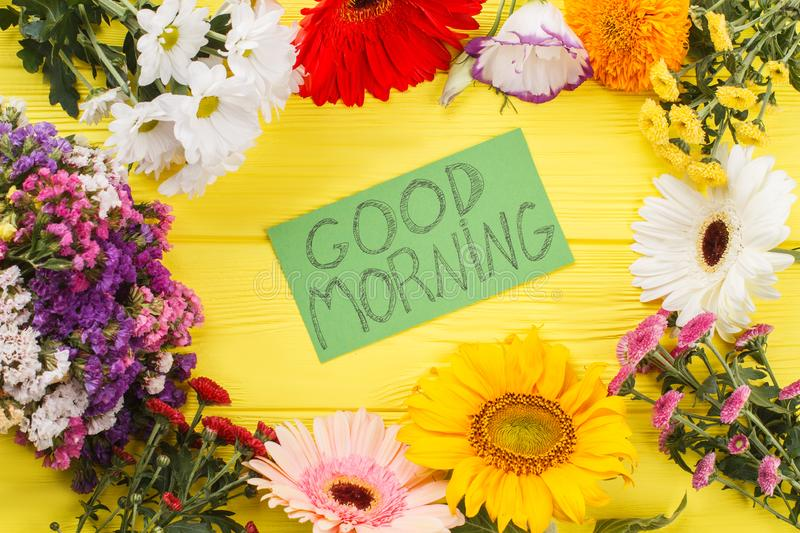 Lovely good morning wish and flowers. Yellow wooden desk background stock images