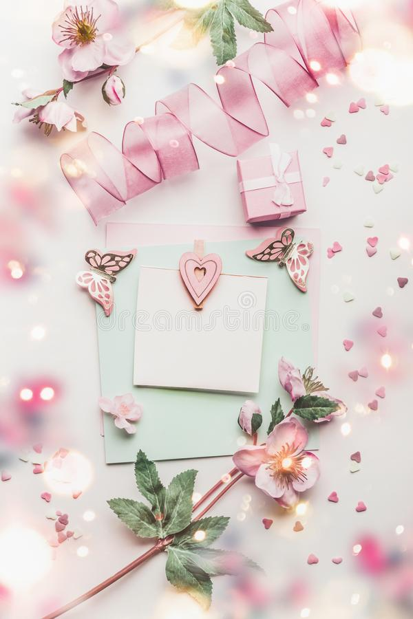 Lovely greeting card composition in pastel color with mock up, flowers and little gift box, hearts and handicraft decoration. Accessories, top view royalty free stock photos