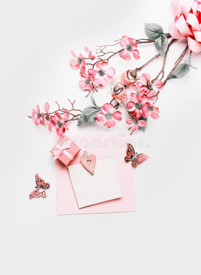 Lovely greeting card mock up with flowers, ribbon, little gift box and hearts in coral color on white background, top view. Flat. Lay. Abstract love and stock photos