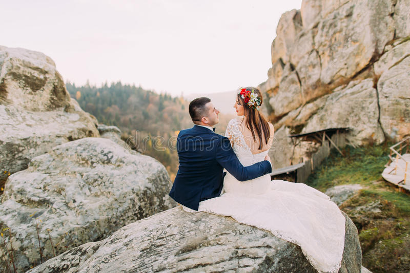 Lovely groom in stylish blue suit holding white dressed bride with cute head wreath on majestic mountain rocky landscape stock image
