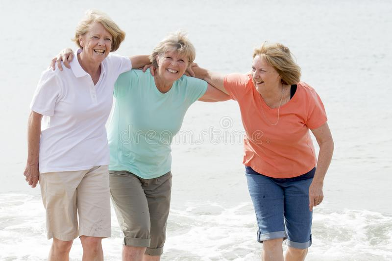 Lovely group of three senior mature retired women on their 60s having fun enjoying together happy walking on the beach smiling pla. Yful in female friendship and stock photo