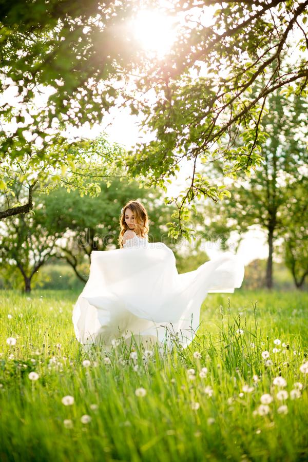 Lovely, happy bride walking in a park after marriage royalty free stock photography