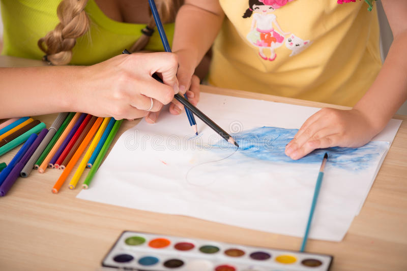Lovely happy family drawing and painting at home. Closeup portrait of lovely happy family drawing and painting at home together, pens and paints, drawing by the stock photography