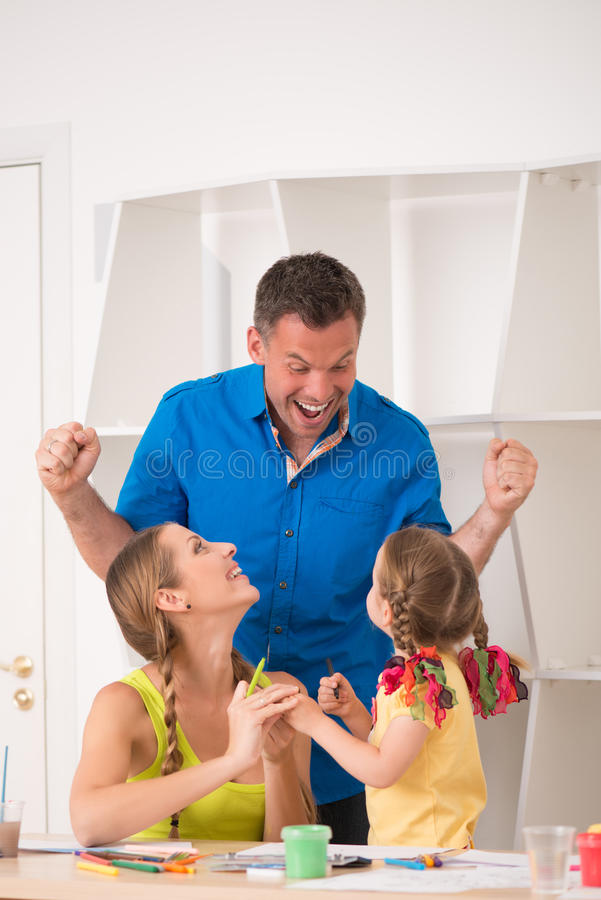 Lovely happy family drawing and painting at home. Half length portrait of lovely happy family drawing and painting at home together, father raising hands and stock image