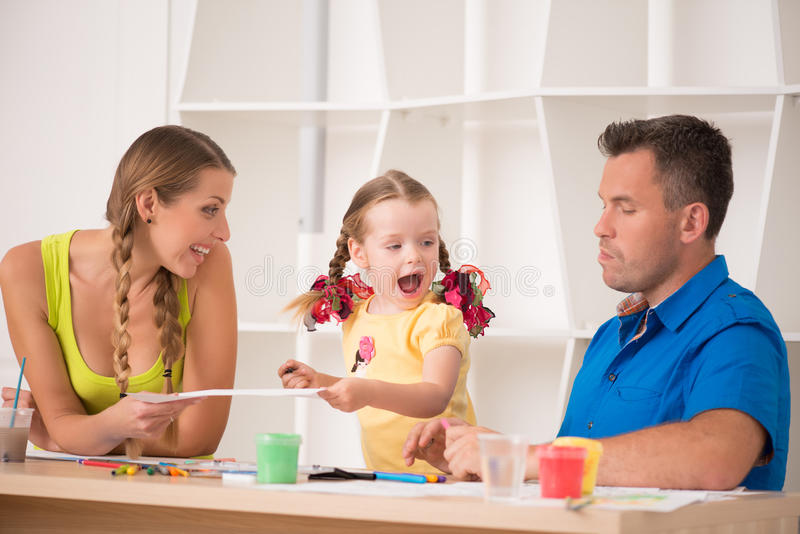 Lovely happy family drawing and painting at home. Half length portrait of lovely happy family drawing and painting at home together, laughing and having fun stock image