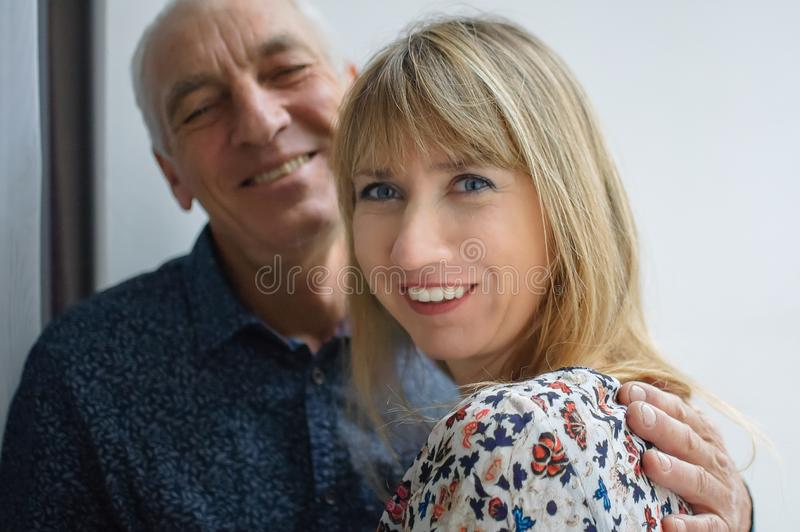 Lovely happy portrait of elderly man hugging his young blonde-haired smiling wife wearing warm dress. Couple with age royalty free stock photography