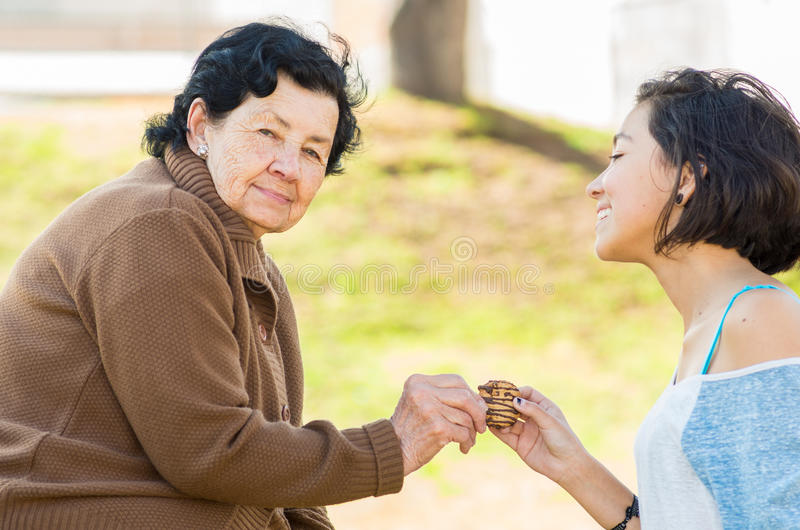 Lovely hispanic grandmother and granddaughter. Enjoying quality time outdoors sharing snacks stock photography