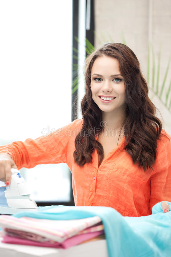 Lovely housewife with iron stock photo