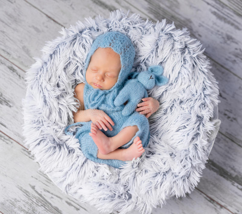 Lovely infant in hat and jumpsuit sleeping on round bed stock photo