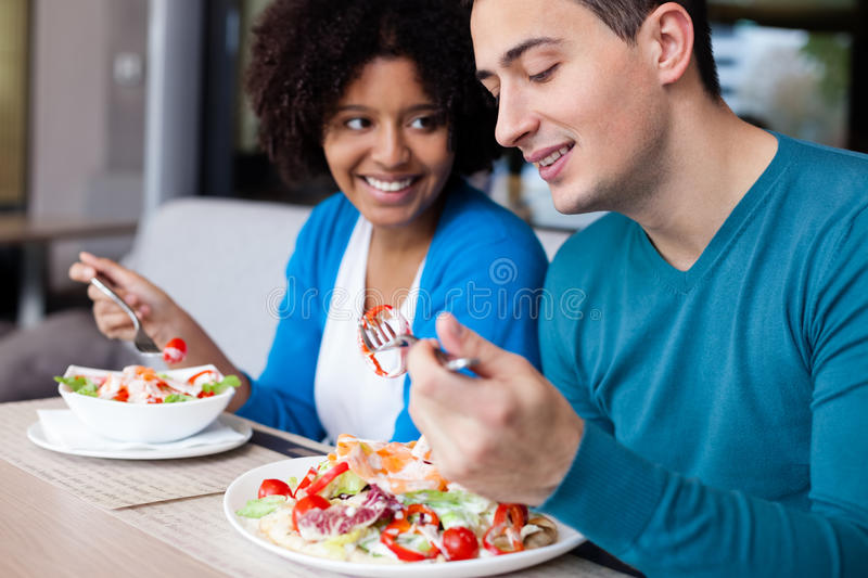 Lovely interracial couple having lunch. At restaurant stock photography
