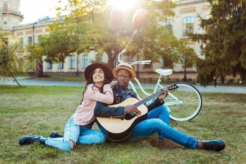 Lovely interracial Couple sitting with a guitar royalty free stock photography