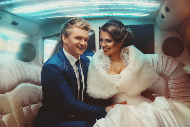 Lovely just merried couple driving in limousine royalty free stock photography