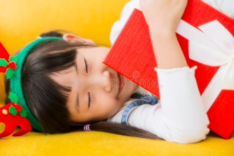 Lovely kid girl smiling eye close arm hug new year gift. Box with soft dream effect stock image