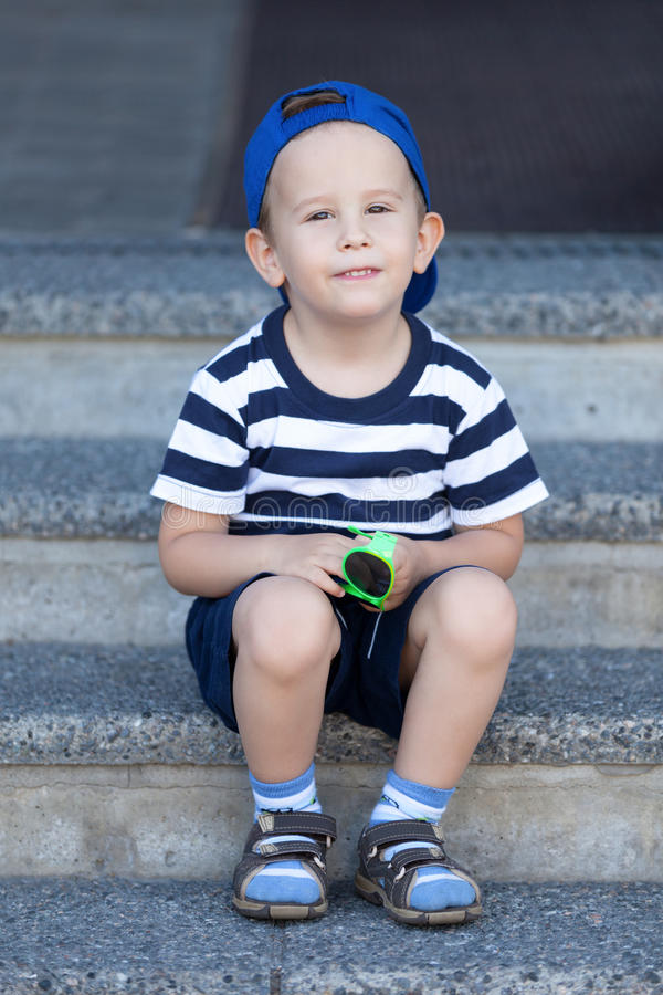 Lovely kid waiting for a walk. Lovely kid sitting on the stairs and waiting for a walk stock images