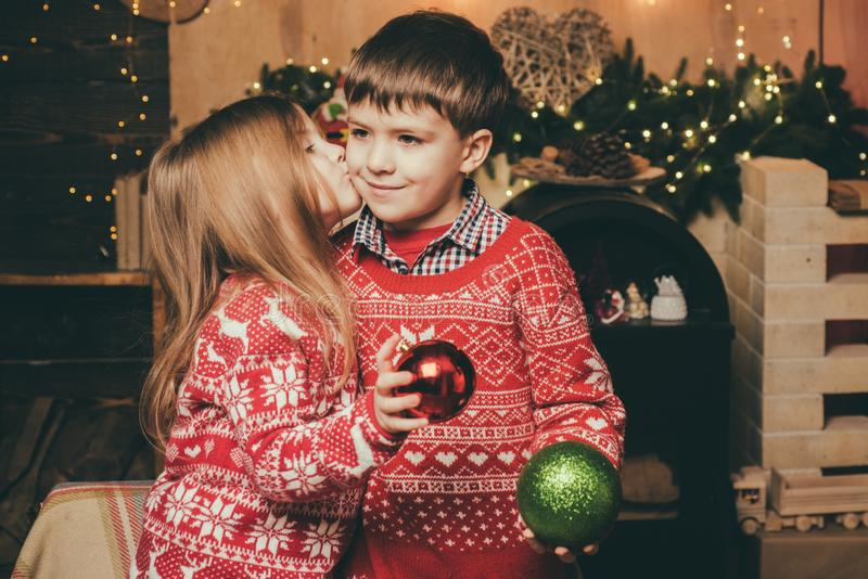 Lovely kiss. Cute little girl and boy play ornaments balls christmas tree. Kid enjoy winter holiday at home. Cozy royalty free stock images