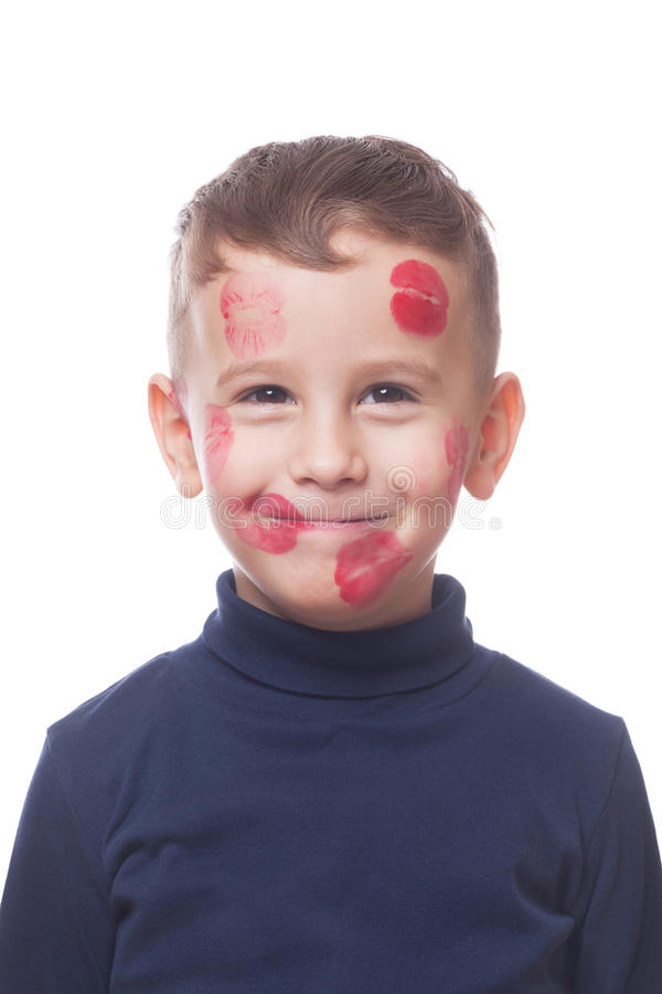 Lovely kissed boy. Lovely smiling boy with kissed all around face on isolated white royalty free stock photo