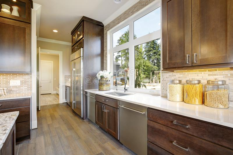 Lovely kitchen with high-end appliances. Lovely kitchen features wood cabinets fitted with high-end appliances paired with a white quartz countertop fitted with royalty free stock image