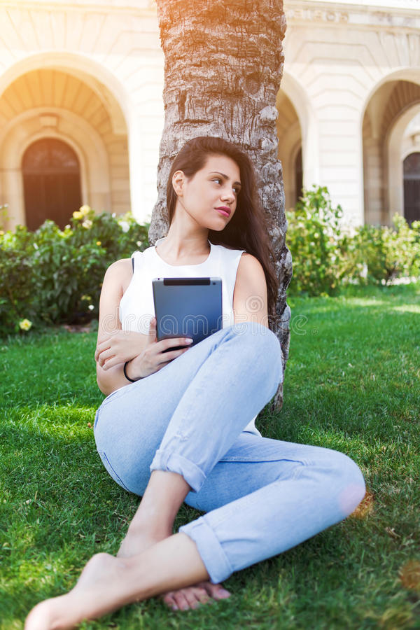 Lovely latin female is using tablet computer while relaxing outdoors in spring day stock images