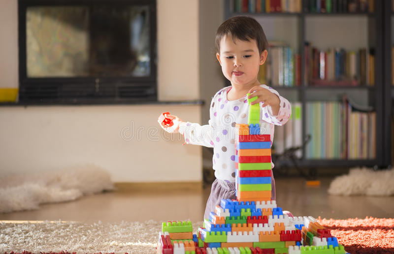 Lovely laughing little child, brunette girl of preschool age playing with colorful blocks sitting on a floor stock image