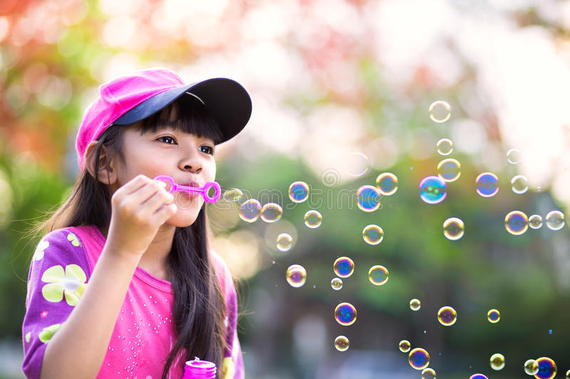 Lovely little asian girl blowing soap bubbles royalty free stock photo