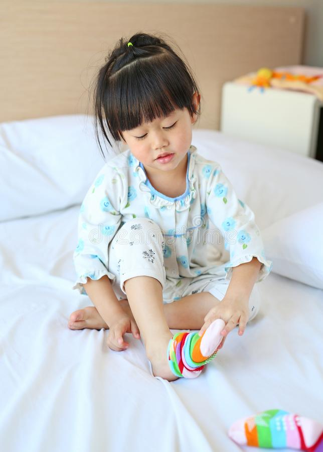 Lovely little asian girl trying to put a socks on the bed royalty free stock images