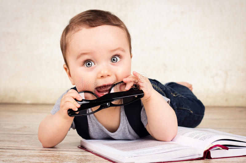 Lovely little baby boy with glasses reading a book royalty free stock photo