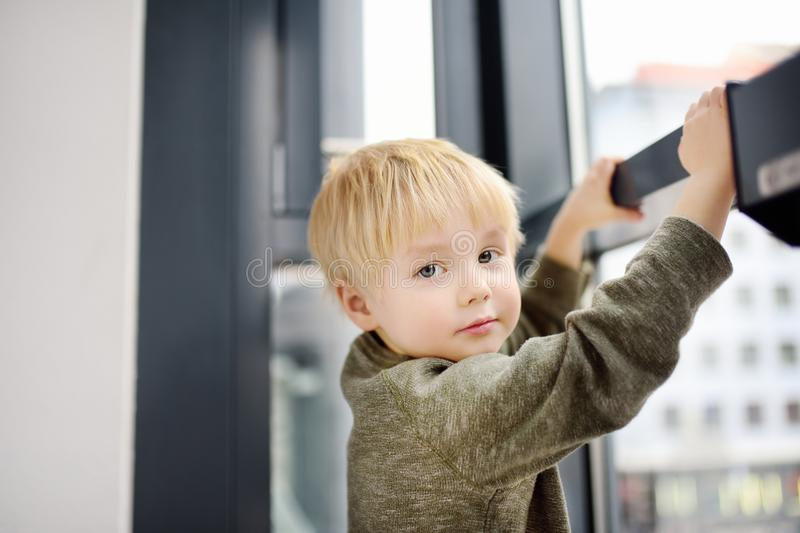Lovely little boy sitting on the window near panoramic window and looking outside stock photography