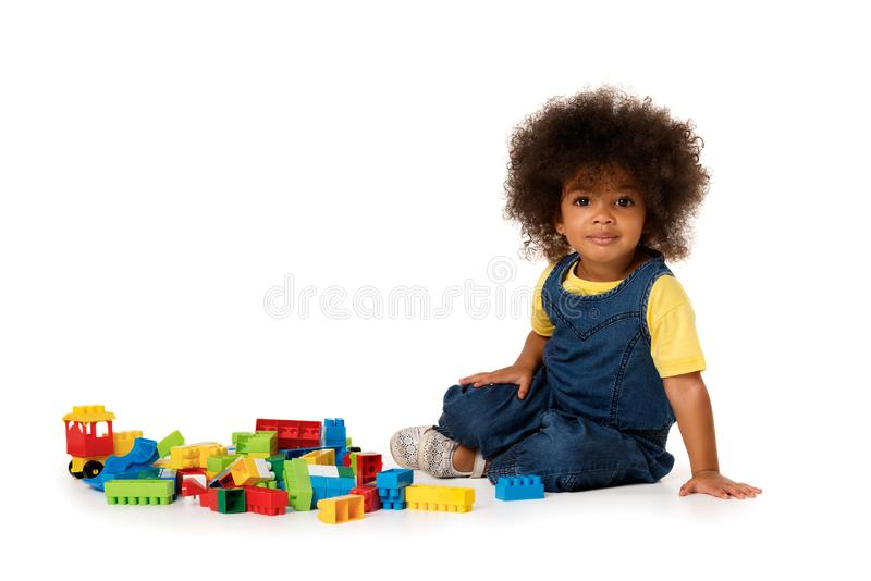 Lovely little cute african american girl on the floor with lots of colorful plastic blocks in studio, isolated stock image