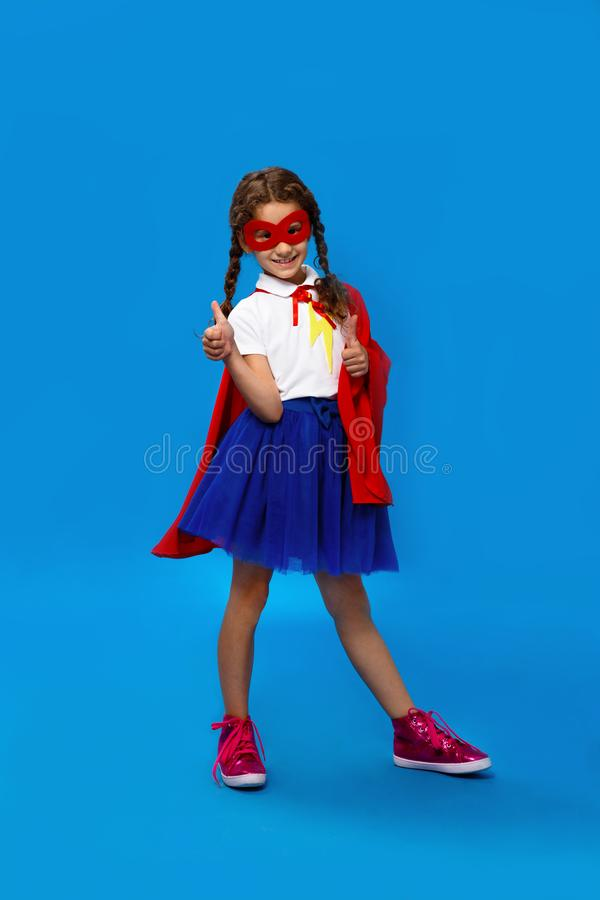 Lovely little girl in adorable superhero costume showing a thumb up, looking at camera, on blue background. Copy space. royalty free stock photo